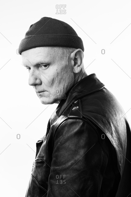 Older man wearing leather jacket and knit hat looking over his shoulder in black and white