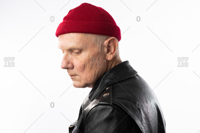 Profile view of an older man wearing leather jacket and red knit hat looking sad