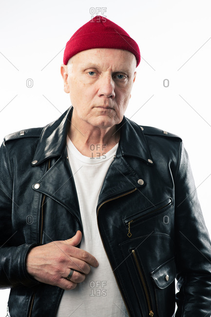Senior man wearing leather jacket and red knit hat looking at camera