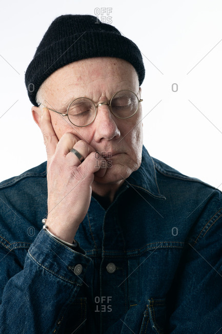 Senior man wearing a jean jacket and knit hat with his eyes closed