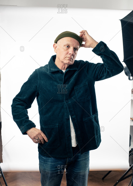 Senior man wearing a corduroy jacket and a knit hat at a photo shoot