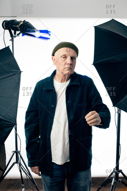 Older man wearing a corduroy jacket and a knit hat at a photo shoot