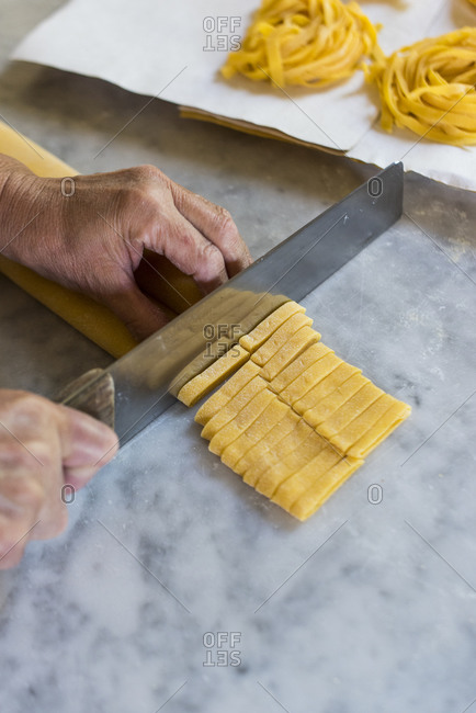 Italian woman making homemade Tagliatelle pasta