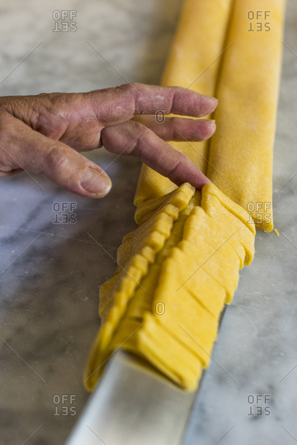 Italian woman making homemade Tagliatelle pasta on a marble surface