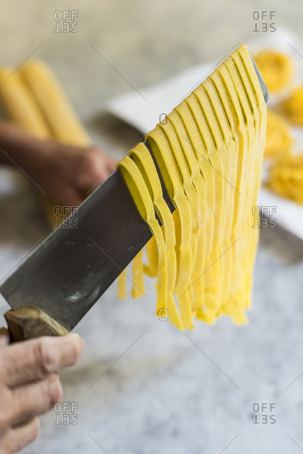 Close up of an Italian woman making homemade Tagliatelle pasta