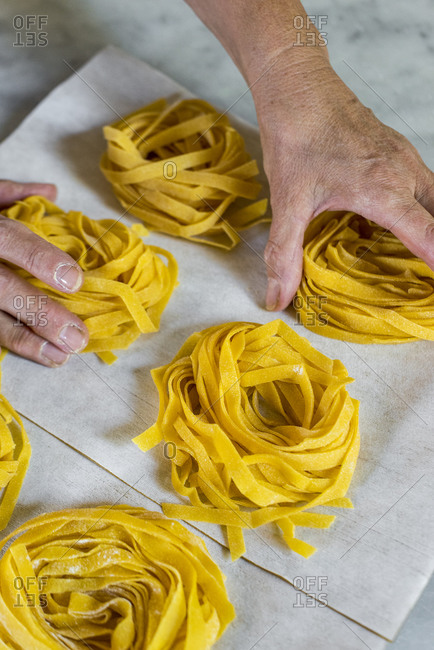 Chef arranging bunches of fresh homemade Tagliatelle pasta into round piles