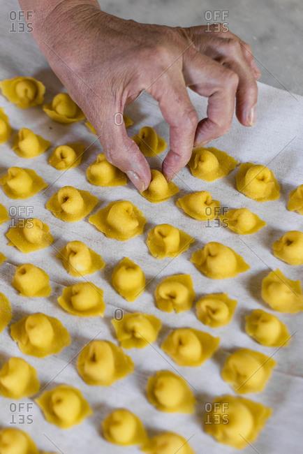 Italian woman making homemade tortellini pasta
