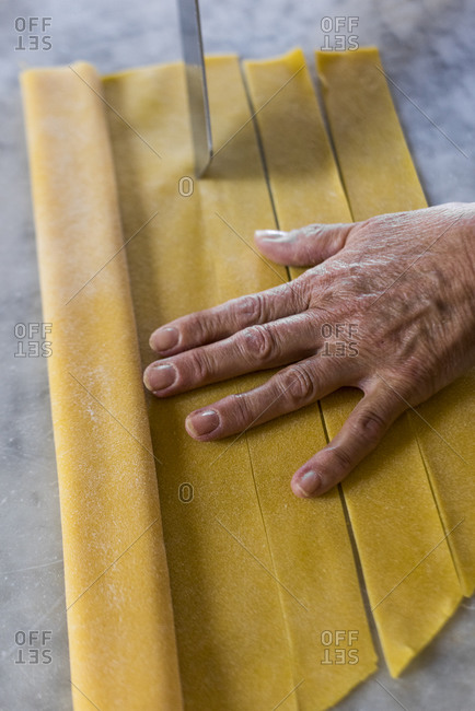 Italian woman cutting pieces of homemade pasta dough for tortellini