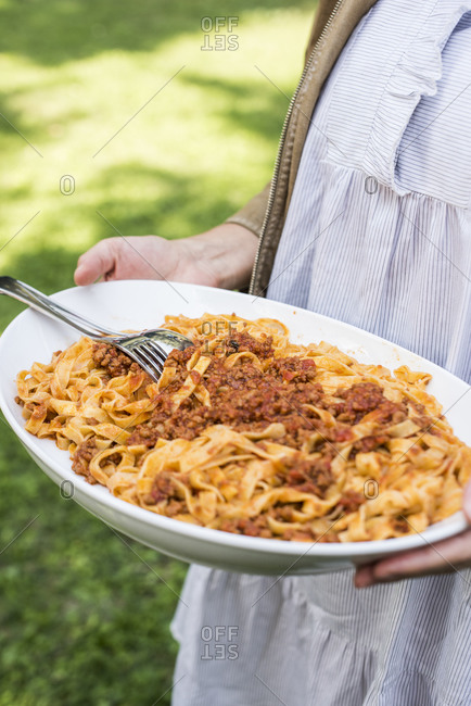 Woman holding platter of homemade Tagliatelle pasta with meat sauce