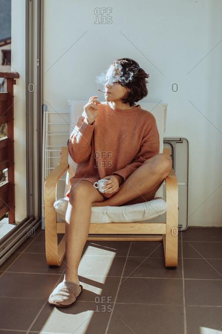 Woman sitting on balcony smoking a cigarette