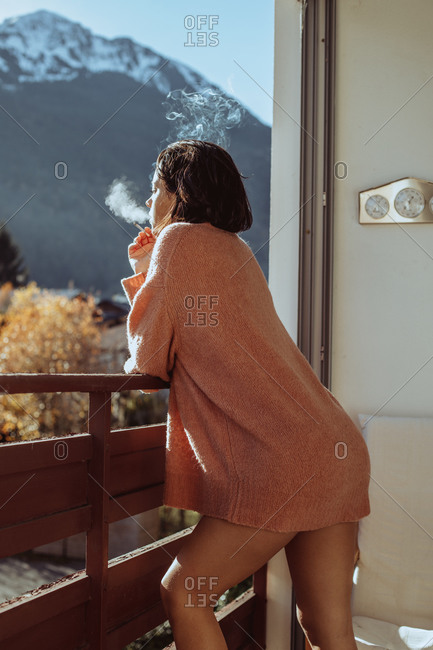 Woman on balcony smoking a cigarette and looking out at mountain