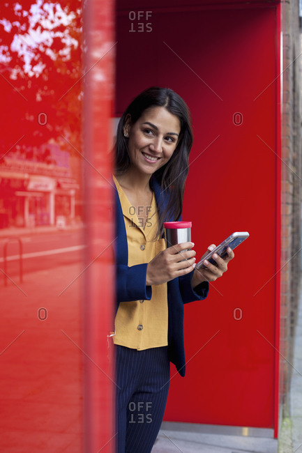 Young businesswoman with reusable coffee cup and smartphoneleaning on wall
