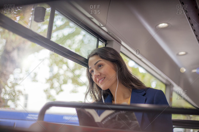 Young woman listening music on a bus with earphones- looking out of window