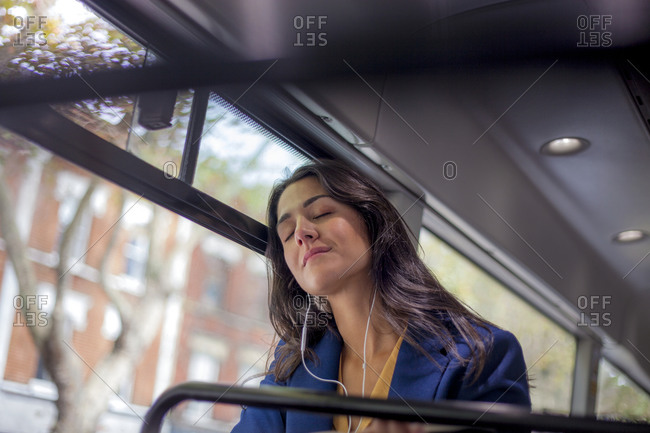 Young woman listening music on a bus with earphones- eyes closed