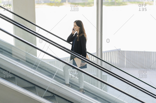 Smiling businesswoman on escalator talking on the phone