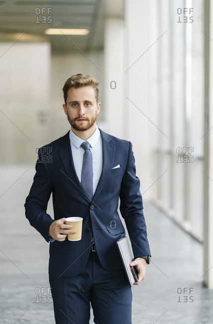 Portrait of businessman holding takeaway coffee