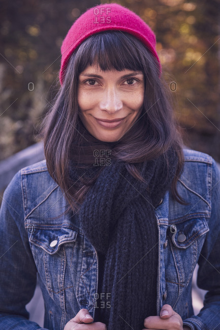 Portrait of smiling woman wearing red woolly hat and denim jacket