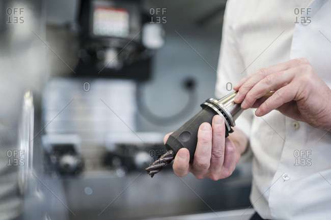 Close-up of man holding drill head in a factory