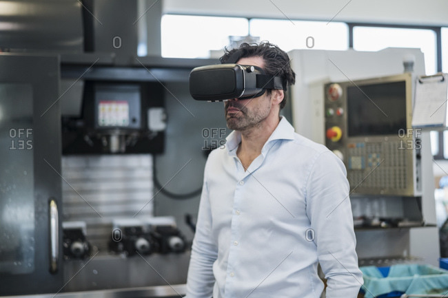 Businessman wearing VR glasses in a factory