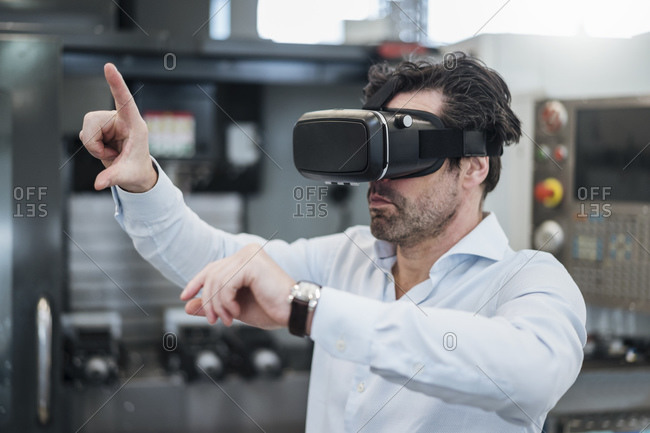 Businessman using VR glasses in a factory