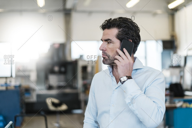 Businessman on the phone in a factory