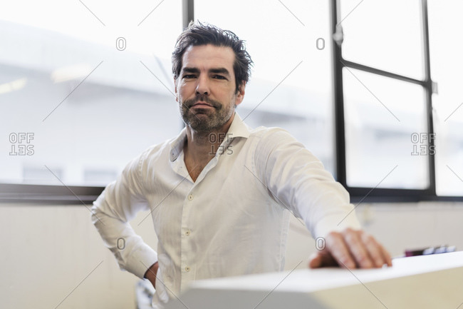 Portrait of a confident businessman at the window in a factory