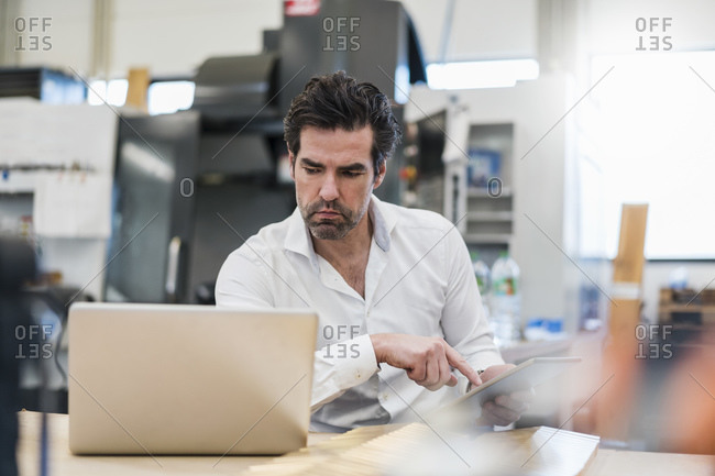 Businessman using tablet and laptop in a factory