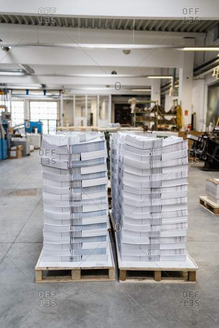 Stacks of papers on pallets in a printing shop