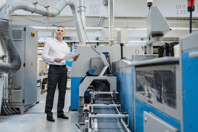 Businessman holding paper in a factory