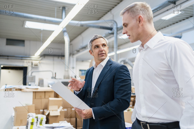 Two businessmen with paper talking in a factory