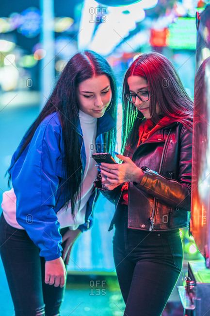 Two teenage girls sharing smartphone on a funfair at night