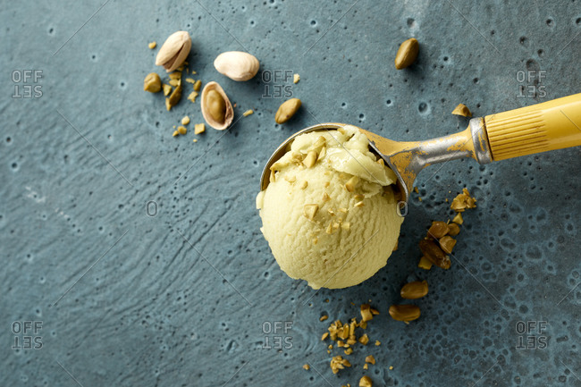 Pistachio ice cream on scoop and nuts