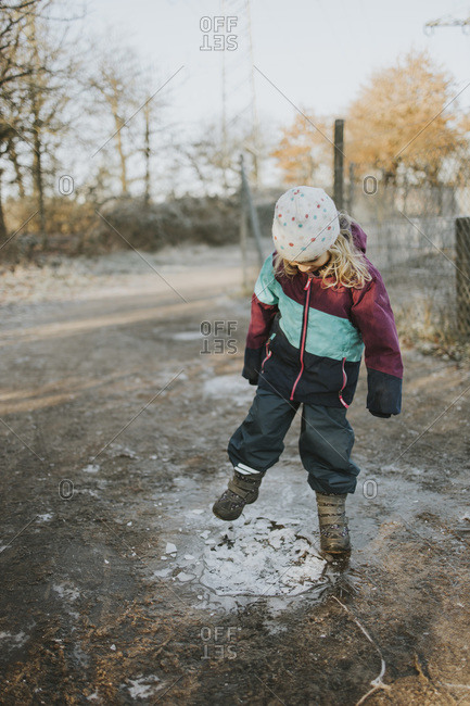 Girl kicking on frozen puddle