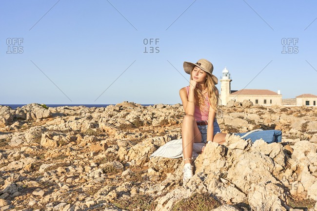 Young woman sitting on rocky beach- relaxing- Menorca- Spain