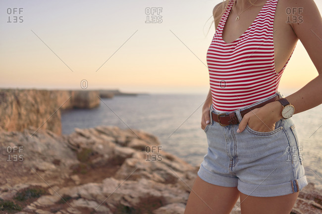 Young woman enjoying sunset at the sea- standing on cliff