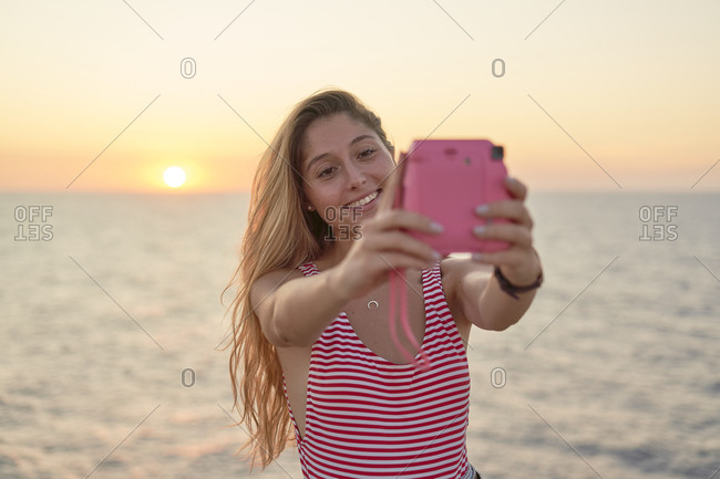 Young woman taking pictures of herself at sunset by the sea