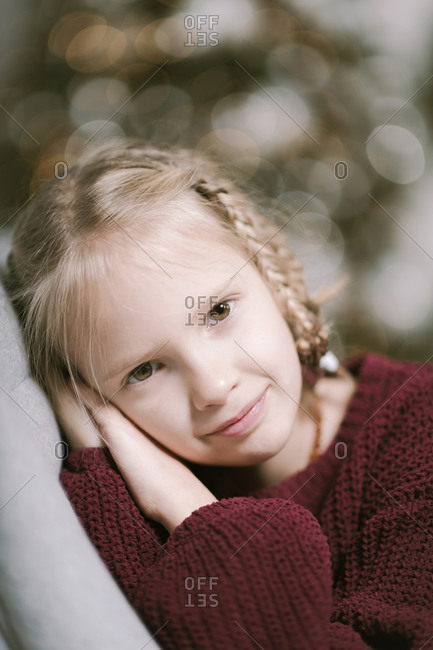 Portrait of blond little girl wearing ruby knit pullover at home