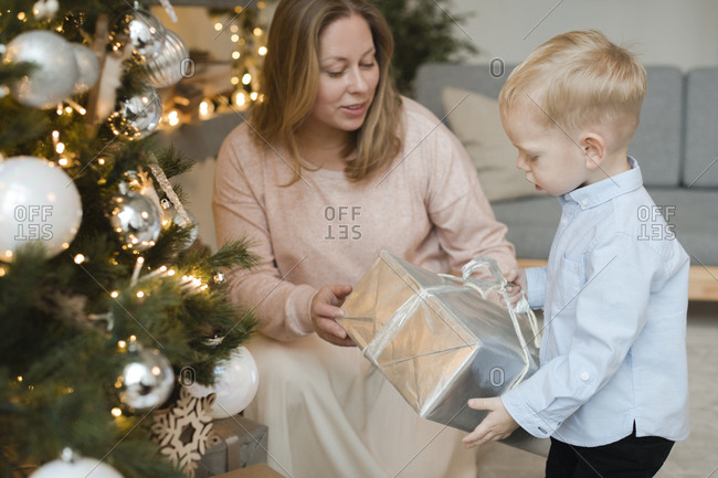 Mother giving present to her little son near Christmas tree