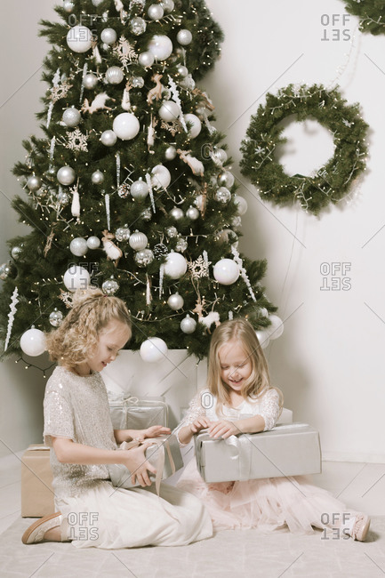 Two little girls sitting in front of Christmas tree opening Christmas presents