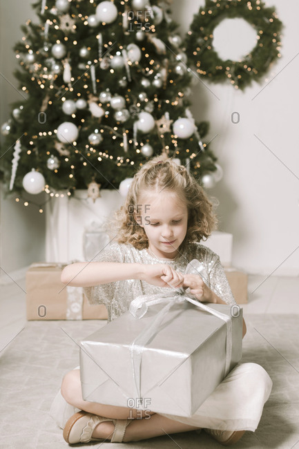 Portrait of blond little girl sitting in front of Christmas tree opening Christmas present