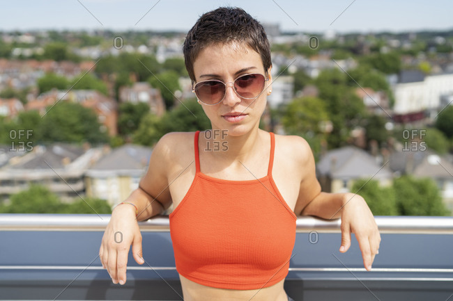 Portrait of woman on roof terrace wearing orange top and sunglasses