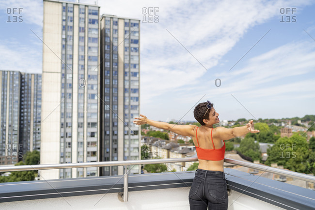 Back view of happy woman standing on roof terrace with arms outstretched