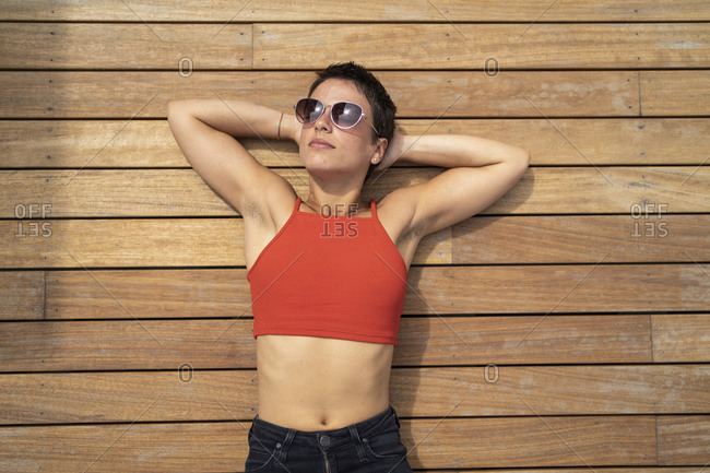 Portrait of woman wearing sunglasses lying on wooden floor of terrace relaxing
