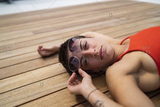 Portrait of woman with sunglasses lying on wooden floor of terrace