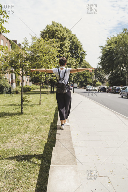 Back view of woman with backpack balancing on a wall