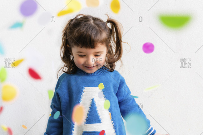 Happy little girl with the confetti during a party in front of a white wall