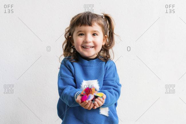 Happy little girl blowing the confetti at a party in front of a white wall
