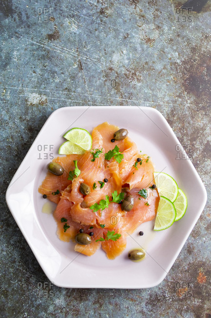 Raw salmon meat with lime- olives and herbs