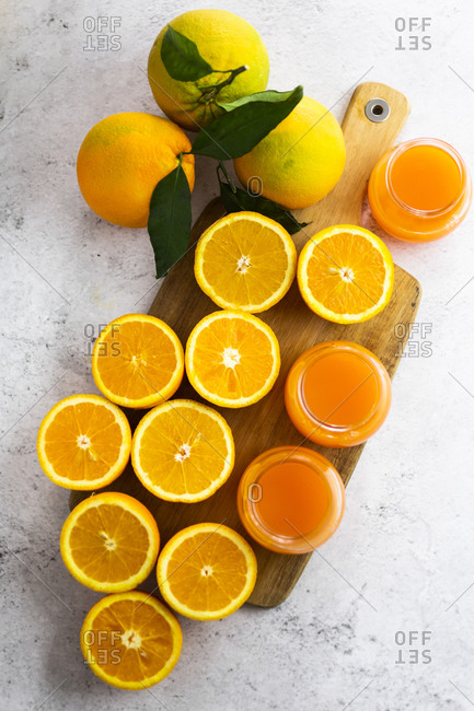 Freshly cut oranges and jars of orange juice on cutting board
