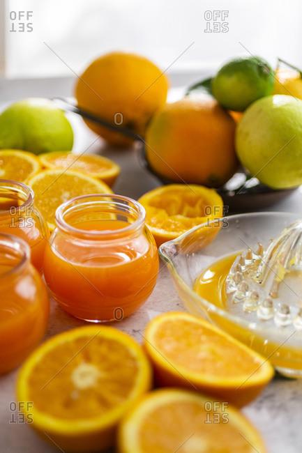 Freshly cut oranges and jars of orange juice